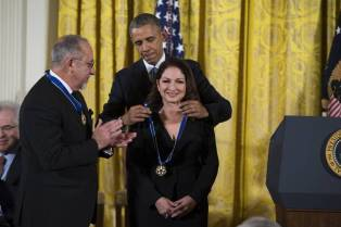 Gloria Estefan getting the Presidential Medal of Freedom from President Obama, while Emilio Estefan looks on.